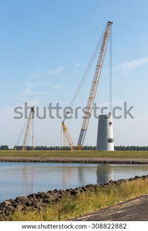 Big crane busy with construction of a new windturbine in the Netherlands - stock photo