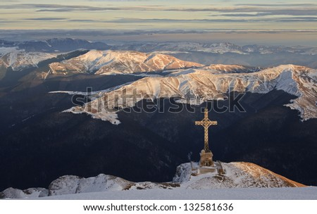 Big cross above the mountains shining in sunset - stock photo