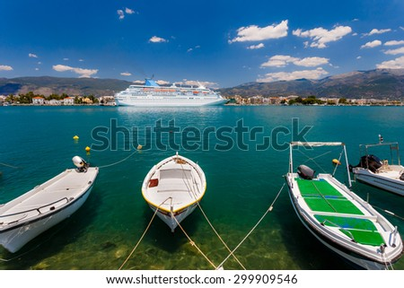 Big cruise ship anchored in port with small fish boats in the foreground against a blue sky and clouds in Greece - stock photo