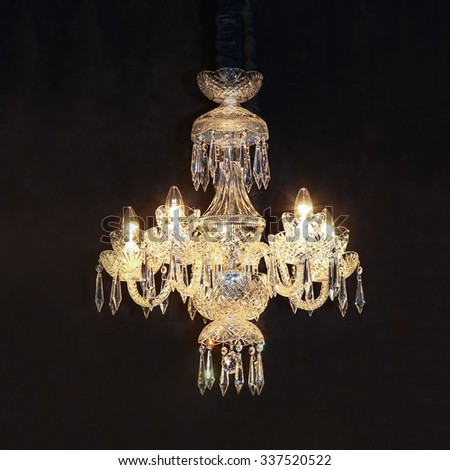 Big crystal glass chandelier at black background - stock photo