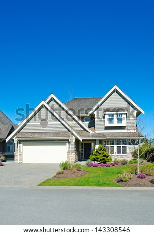 Big custom made luxury double garage doors house with nicely trimmed and landscaped front yard in the suburbs of Vancouver, Canada. - stock photo