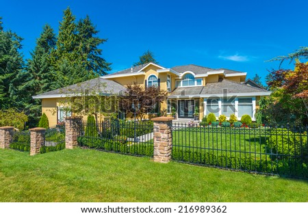 Big custom made luxury house behind the metal fence and nicely landscaped front yard and driveway to garage in the suburbs of Vancouver, Canada. - stock photo