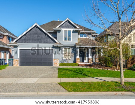 Big custom made luxury house, house entrance with nicely trimmed and landscaped front yard and driveway to garage in the suburbs of Vancouver, Canada. - stock photo
