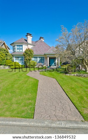 Big custom made luxury house with long doorway and nicely trimmed front yard in the suburbs of Vancouver, Canada. Vertical. - stock photo