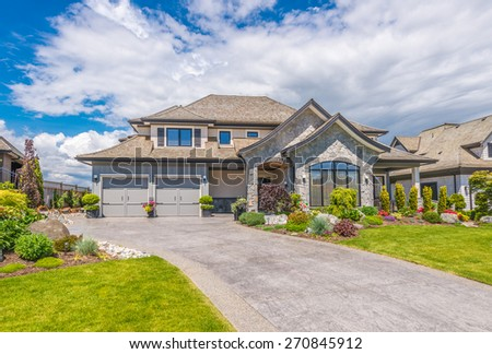 Big custom made luxury house with nicely landscaped front yard and  driveway to the garage in the suburb of Vancouver, Canada. - stock photo
