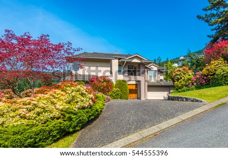 Big custom made luxury house with nicely landscaped front yard and  driveway to the garage in the suburbs of Vancouver, Canada.