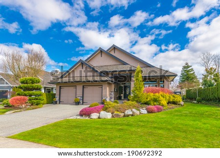 Big custom made luxury house with nicely landscaped front yard, double doors garage and long and wide driveway in the suburbs of Vancouver, Canada.