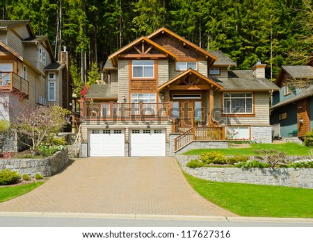 Big custom made luxury house with nicely landscaped front yard in the suburbs of North Vancouver, Canada. - stock photo