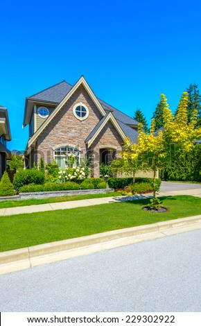 Big custom made luxury house with nicely landscaped front yard in the suburbs of Vancouver, Canada. Vertical.