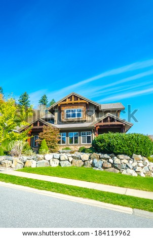 Big custom made luxury house with nicely landscaped with some rocks front yard in the suburbs of Vancouver, Canada. Vertical. - stock photo