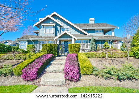 Big custom made luxury house with nicely paved and stoned doorway and trimmed and landscaped front yard in the suburbs of Vancouver, Canada.