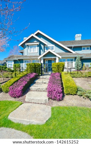 Big custom made luxury house with nicely paved and stoned doorway and trimmed and landscaped front yard in the suburbs of Vancouver, Canada. - stock photo
