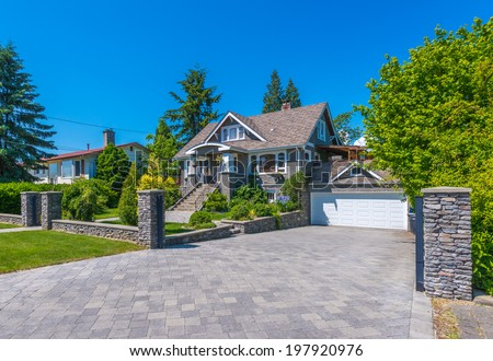 Big custom made luxury house with nicely paved driveway to the double doors garage in the suburb of Vancouver, Canada. - stock photo