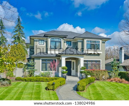 Big custom made luxury house with nicely paved long doorway and trimmed front yard in the suburbs of Vancouver, Canada. - stock photo