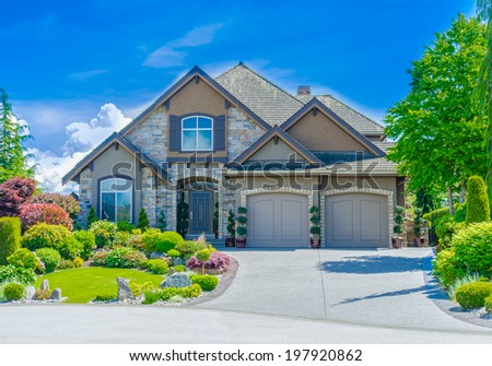 Big custom made luxury house with nicely trimmed and landscaped front yard and driveway to the double doors garage in the suburb of Vancouver, Canada. - stock photo