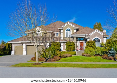 Big custom made luxury house with nicely trimmed and landscaped front yard and garages in the suburbs of Vancouver, Canada. Vertical. - stock photo