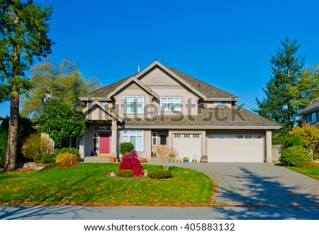 Big custom made luxury house with nicely trimmed and landscaped front yard in the suburb of Vancouver, in colorful fall time. Canada. - stock photo