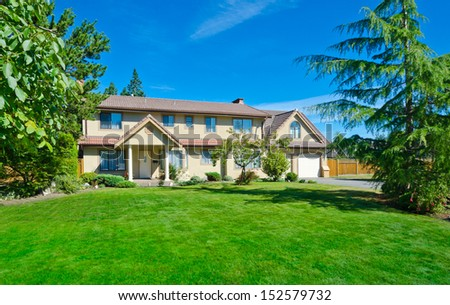 Big custom made luxury house with nicely trimmed front yard lawn in the suburbs of Vancouver, Canada.