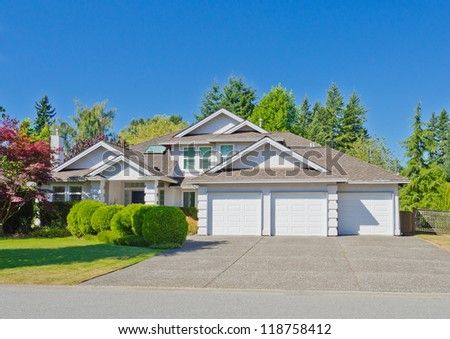 Big custom made luxury house with the triple garage doors  in the suburbs of Vancouver, Canada.
