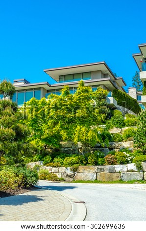 Big custom made luxury modern house on the rocks with nicely landscaped front yard in the suburbs of Vancouver, Canada. Vertical. - stock photo