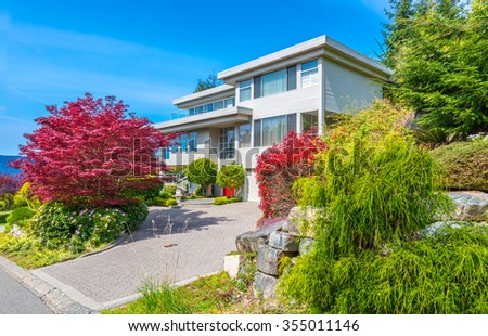 Big custom made luxury modern house with nicely landscaped front yard and  driveway to the garage in the suburbs of Vancouver, Canada.