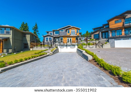 Big custom made luxury modern house with nicely landscaped  front yard and paved driveway to garage in the suburbs of Vancouver, Canada. - stock photo
