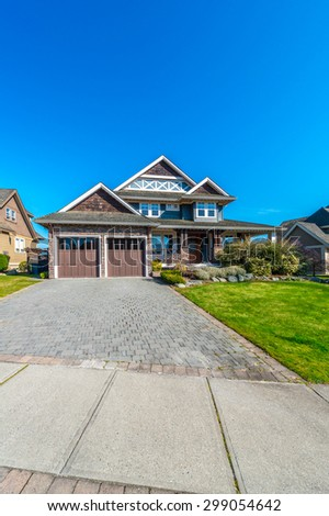 Big custom made luxury modern house with paved driveway and  nicely landscaped front yard in the suburbs of Vancouver, Canada. Vertical. - stock photo