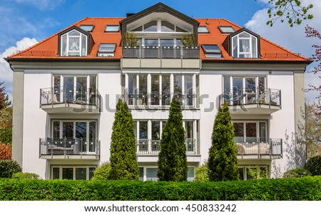 Big custom made luxury three-storey house with a brown tile roof and green hedges - a typical traditional austrian (german) building in a residential neighborhood. Small balconies on facade. - stock photo