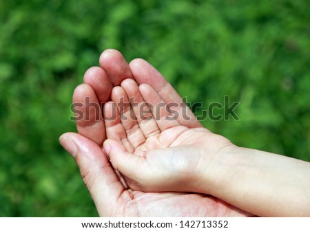 Big Daddy's hand holding the hand of her baby - stock photo