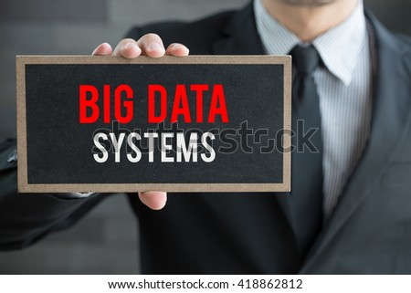 Big data systems, message on blackboard and hold by businessman - stock photo