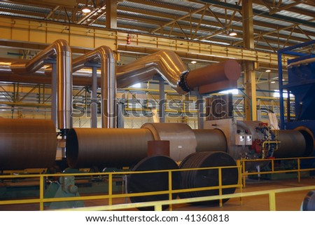 Big diameter steel pipes production in ferrous metallurgy work by weld machine - stock photo