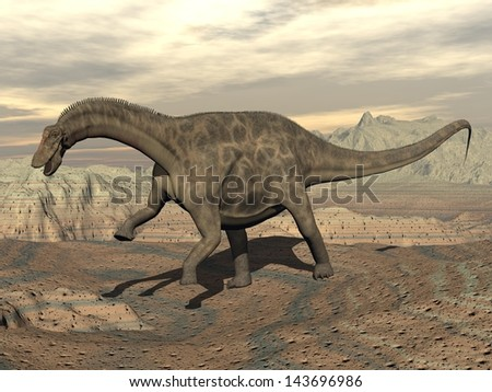 Big dicraeosaurus dinosaur walking in the rocky desert by cloudy day - stock photo