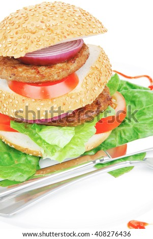 big double hamburger on ceramic plate with cutlery isolated  over white background