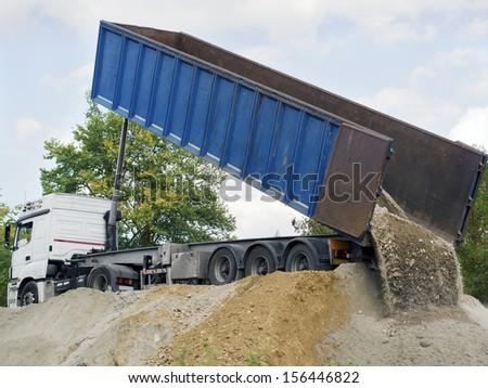 big dump truck downloading terrain - stock photo