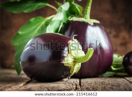 Big Eggplants in Country Composition on wooden background, still life - stock photo