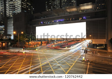 Big Empty Billboard at night in city with busy traffic - stock photo