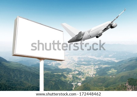 Big empty billboard with copy space for your image or text with an airplane flying on the sky, ideal for travel or vacation promotions - stock photo
