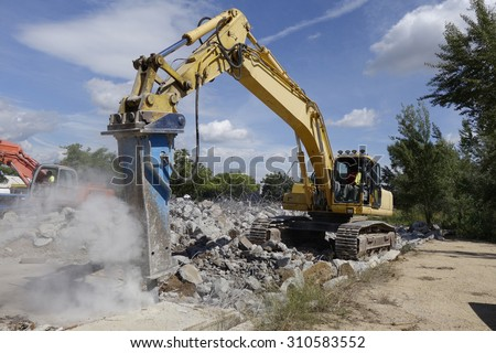 Big excavator with hammer, for concrete demolition                             - stock photo