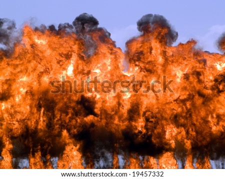 Big explosion fire rising high on blue sky - stock photo