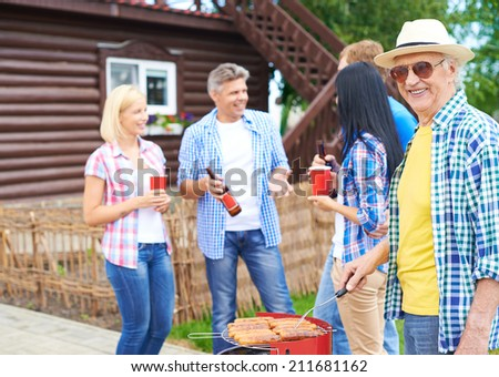 Big family grilling sausages at their village - stock photo