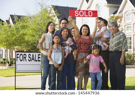 Big family holding up Sold sign in front of house - stock photo