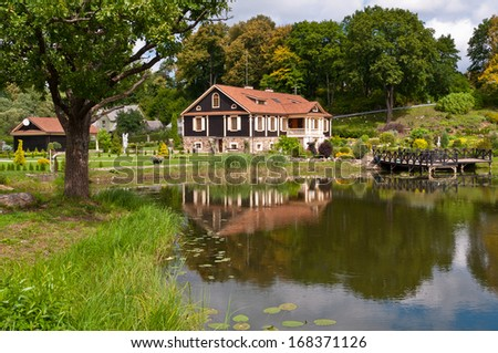 Big Family House in Front of the Lake in the Forest - stock photo