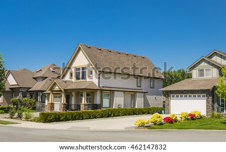Big family house with concrete driveway to double size garage. Residential house with door steps to the entrance under the porch