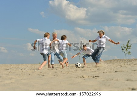 big Family playing football on a beach in summer day