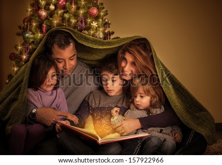 Big family reading interesting magic story in Xmas eve, happy parents with cheerful children covered with blanket, Christmas tree at home, New Year celebration - stock photo