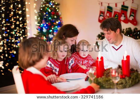 Big family with three children celebrating Christmas at home. Festive dinner at fireplace and Xmas tree. Parent and kids eating at fire place in decorated room. Child lighting advent wreath candle