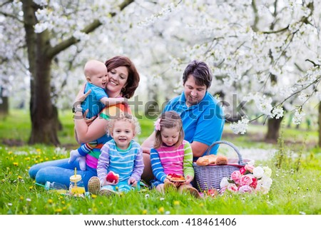 Big family with three little children eating lunch outdoors. Parents and kids with picnic basket in spring garden. Mother, father, preschooler girl, toddler boy and baby eat and drink in summer park. - stock photo
