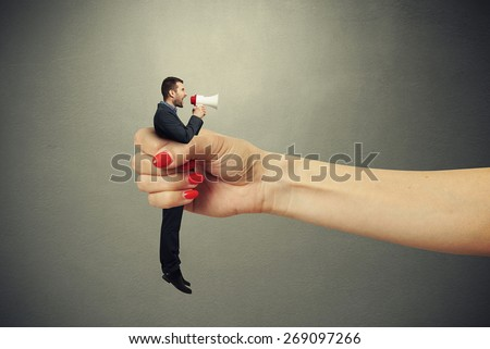 big female hand holding in fist small man and he screaming at megaphone. photo on dark background - stock photo