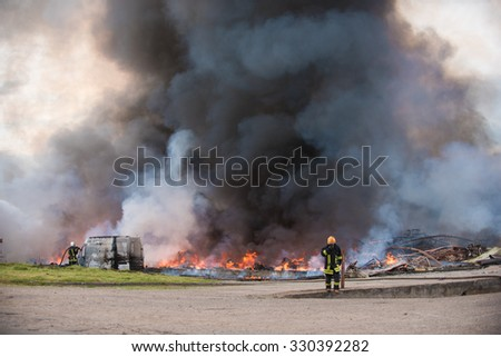 Big fire of buildings and cars. Smoke coming up to the sky. Firemen at work. - stock photo