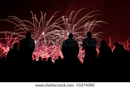 Big fireworks with silhouetted people in the foreground watching - stock photo
